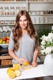 Uśmiechnięta ładna kobieta robi sokowi pomarańczowemu Fotografia Stock