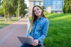 Uśmiechnięta ładna kobieta w przypadkowych ubraniach z laptopem na ona nogi ja fotografia royalty free
