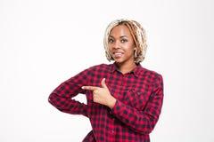 Uśmiechnięta ładna młoda amerykanin afrykańskiego pochodzenia kobieta wskazuje daleko od obrazy royalty free