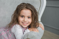 Uśmiechnięta ładna mała dziewczynka na popielatej kanapie Obraz Stock