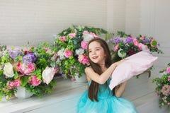 Uśmiechnięta ładna mała dziewczynka w sukni turkusowych chwytach w ręki poduszka w studiu z kwiaty Zdjęcie Stock