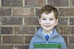 Uśmiechnięta śliczna chłopiec up przeciw ściana z cegieł obrazy royalty free