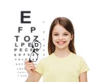 Uśmiechnięta śliczna mała dziewczynka trzyma czarnych eyeglasses obrazy stock