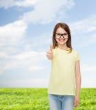 Uśmiechnięta śliczna mała dziewczynka w czarnych eyeglasses Fotografia Stock