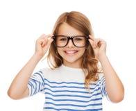 Uśmiechnięta śliczna mała dziewczynka z czarnymi eyeglasses fotografia stock