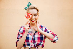 Uśmiechnięta śliczna szpilka w górę dziewczyny pokrywy z lizakiem jej oko Zdjęcia Royalty Free