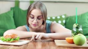 Uśmiechnięta śmieszna młoda kobieta bawić się palce na stole wybiera między zdrowym i niezdrowym jedzeniem zdjęcie wideo