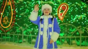 Uśmiechnięta śnieżna dziewczyna macha jego rękę przy choinką zdjęcie wideo
