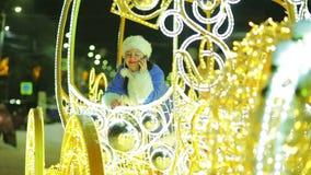 Uśmiechnięta śnieżna dziewczyna opowiada na telefonie i macha powitanie z karecianego okno w powitaniu zbiory wideo