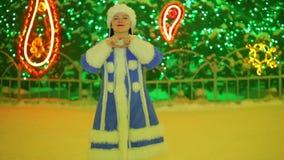 Uśmiechnięta śnieżna dziewczyna pokazuje serce przy choinką zbiory wideo