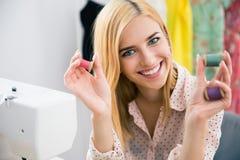 Uśmiechnięta żeńska deisgner mienia nić Zdjęcia Stock
