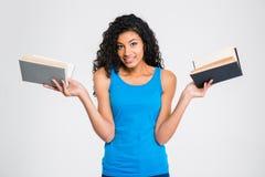 Uśmiechnięta afro amerykańska kobieta trzyma dwa książki Zdjęcia Stock