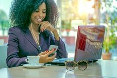 Uśmiechnięta afrykańska kobieta pije kawę używać laptop i mądrze telefon Fotografia Royalty Free