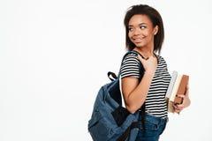 Uśmiechnięta afrykańska nastolatek dziewczyna jest ubranym plecaka i patrzeje daleko od Zdjęcia Stock