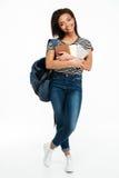 Uśmiechnięta afrykańska nastolatek dziewczyna jest ubranym plecaka i trzyma książki Fotografia Royalty Free
