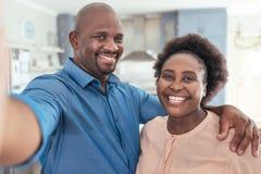 Uśmiechnięta Afrykańska para bierze selfie wpólnie w domu Zdjęcia Royalty Free