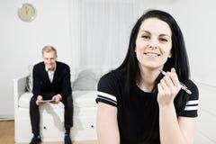 Uśmiechnięta aktywna kobieta pracuje przy biurkiem i eleganckim mężczyzny czekaniem w tle fotografia royalty free