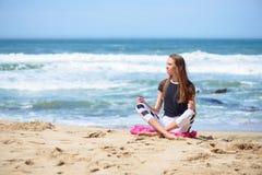 Uśmiechnięta aktywna młoda kobieta robi joga na plaży Obrazy Stock