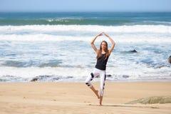 Uśmiechnięta aktywna młoda kobieta robi joga na plaży Zdjęcia Stock