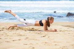 Uśmiechnięta aktywna młoda kobieta robi sportów ćwiczeniom na plaży Fotografia Royalty Free