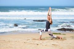 Uśmiechnięta aktywna młoda kobieta robi sportów ćwiczeniom na plaży Obrazy Stock