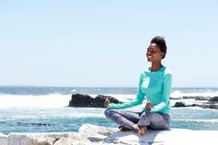 Uśmiechnięta amerykanin afrykańskiego pochodzenia kobieta robi joga morzem Zdjęcie Royalty Free