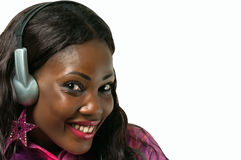 Uśmiechnięta amerykanin afrykańskiego pochodzenia kobieta słucha muzyka z hełmofonem Obrazy Stock