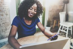 Uśmiechnięta amerykanin afrykańskiego pochodzenia kobieta używa laptop i smartphone przy drewnianym stołem w żywym pokoju podczas obraz stock
