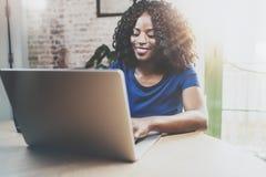Uśmiechnięta amerykanin afrykańskiego pochodzenia kobieta używa laptop przy drewnianym stołem w żywym pokoju podczas gdy siedzący obraz stock