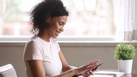 Uśmiechnięta amerykanin afrykańskiego pochodzenia kobieta używa smartphone datowanie app swiping zdjęcie wideo