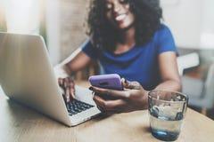 Uśmiechnięta amerykanin afrykańskiego pochodzenia kobieta używa smartphone i laptop przy drewnianym stołem w żywym pokoju podczas zdjęcie royalty free