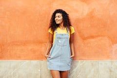 Uśmiechnięta Arabska dziewczyna z czarnej kędzierzawej fryzury przyglądającą lewą stroną obrazy royalty free