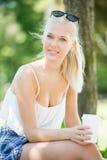 Uśmiechnięta atrakcyjna dziewczyna pije kawę w parku Zdjęcia Stock