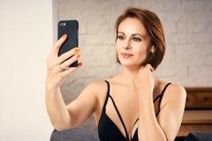 Uśmiechnięta atrakcyjna kobieta bierze selfie i trzyma jej włosy w ręce Zdjęcia Stock