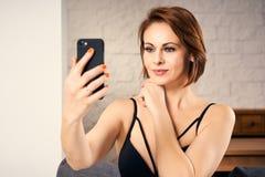 Uśmiechnięta atrakcyjna kobieta bierze selfie podczas gdy siedzący na kanapie w domu Obraz Stock