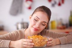 Uśmiechnięta atrakcyjna kobieta ma śniadanie w kuchennym wnętrzu Uśmiechnięta atrakcyjna kobieta Zdjęcia Royalty Free
