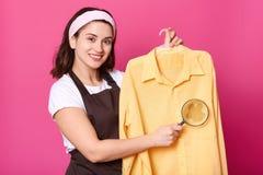 Uśmiechnięta atrakcyjna kobieta trzyma jasnożółtą koszula na wieszaku z białą kapitałką, patrzeje bezpośrednio przy kamerą z szcz obraz stock