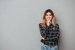 Uśmiechnięta atrakcyjna kobiety pozycja i mienie ręka przy jej podbródkiem obraz royalty free