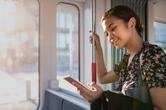 Uśmiechnięta Azjatycka bizneswoman jazda na pociągu używać jej telefon komórkowego obraz stock