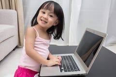 Uśmiechnięta Azjatycka Chińska mała dziewczynka używa laptop w domu Zdjęcia Stock