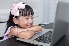 Uśmiechnięta Azjatycka Chińska mała dziewczynka używa laptop w domu Obrazy Royalty Free