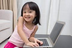 Uśmiechnięta Azjatycka Chińska mała dziewczynka używa laptop w domu Zdjęcie Stock