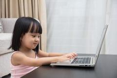 Uśmiechnięta Azjatycka Chińska mała dziewczynka używa laptop w domu Zdjęcie Royalty Free