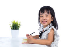 Uśmiechnięta Azjatycka Chińska małego biura damy writing książka Zdjęcie Royalty Free