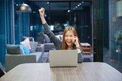 Uśmiechnięta Azjatycka kobieta opowiada na telefonie, używać laptop przy nocą, zdjęcie royalty free