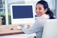 Uśmiechnięta Azjatycka kobieta używa komputerowy przyglądającego z powrotem przy kamerą Obraz Stock