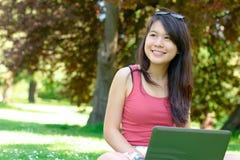 Uśmiechnięta azjatykcia dziewczyna przy parkiem Zdjęcia Royalty Free