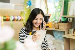 Uśmiechnięta azjatykcia męska kwiaciarnia dzwoni na smartphone i robi notatce Fotografia Royalty Free