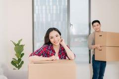 Uśmiechnięta azjatykcia piękna kobieta opiera na pudełkach w nowym domu obrazy stock