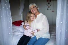 Uśmiechnięta babcia i wnuczka siedzi wpólnie na łóżku zdjęcia royalty free